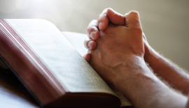 Hands folded in prayer on a Holy Bible in church concept for fai